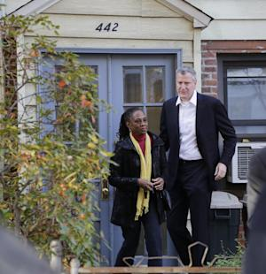 In this Nov. 6, 2013 photo, Chirlane McCray and her husband Bill de Blasio leave their house in the Park Slope neighborhood in the Brooklyn borough of New York. Now de Blasio faces a crucial early decision: should he leave Park Slope behind to move to the mayor's official residence, stately Gracie Mansion on Manhattan's Upper East Side? (AP Photo/Mark Lennihan)