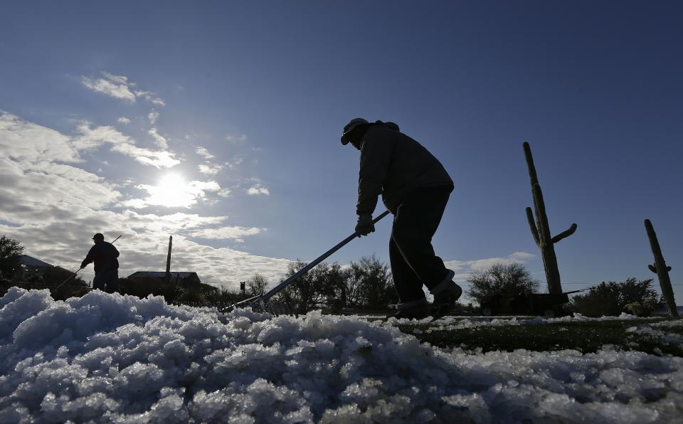 Grounds keeper Tony Lange clears snow off the tenth tee for the Match Play Championship golf tournament, Thursday, Feb. 21, 2013, in Marana, Ariz. A snow storm blanketed the course on Wednesday suspending the first round of play and postponing it until late Thursday morning.  (AP Photo/Ted S. Warren)