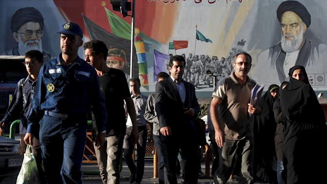 In this picture taken on Wednesday, Sept. 25, 2013, Iranians walk past a huge poster depicting Iranian soldiers during the war with Iraq in the 1980s. Iranian President Hassan Rouhani's outreach to the West is stirring optimism on the streets at home. Many Iranians, even some who did not vote for him, see the efforts at international cooperation as signs that painful sanctions and Iran's isolation could be eased. But hard-liners derailed similar hopes after the election of a reformist president in 1997 and Iran's powerful Revolutionary Guard is warning Rouhani not to go too far, too fast. (AP Photo/Ebrahim Noroozi)