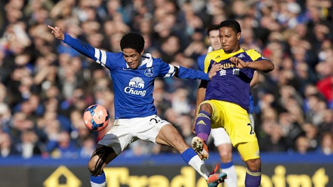Everton's Steven Pienaar, left, fights for the ball against Swansea City's Jonathan de Guzman during their English FA Cup fifth round soccer match at Goodison Park Stadium, Liverpool, England, Sunday Feb. 16, 2014