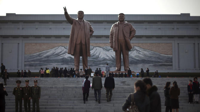 People visit statues of the late North Korean leaders Kim Il Sung, left, and Kim Jong Il to celebrate the 101st birthday of Kim Il Sung in Pyongyang, North Korea, Monday, April 15, 2013. Oblivious to international tensions over a possible North Korean missile launch, Pyongyang residents spilled into the streets Monday to celebrate a major national holiday, the birthday of their first leader. (AP Photo/Alexander F. Yuan)