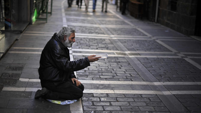 A man begs for alms in a street, in Pamplona, northern Spain, Tuesday, Oct. 30, 2012. Spain's National Statistics Institute says Tuesday that the country's economy contracted 0.3 percent in the third quarter from the previous three month period. Spain is in a double-dip recession and has a 25 percent unemployment rate. Prime Minister Mariano Rajoy said Monday the country has no immediate need to ask for outside aid to help deal with its debts. (AP Photo/Alvaro Barrientos)