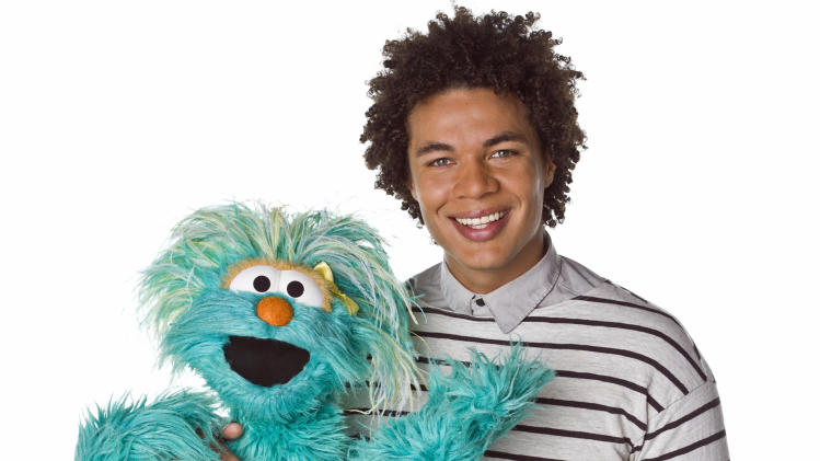 "This April 2013 photo released by Sesame Workshop shows  Puerto Rican actor Ismael Cruz Cordova, 26, of ""Sesame Street,"" posing with muppet Rosita in New York.  Cruz plays Mando, a young Latino writer who interacts with the puppets and also loves technology. (AP Photo/Sesame Workshop, Gil Vaknin)"