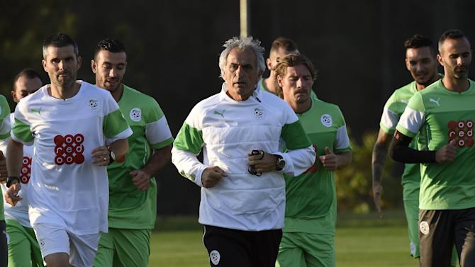 Algeria's coach Vahid Halilhodzic (C) runs with his players during a training session at The Atletico World Sports Centre in Sorocaba, Brazil, during the FIFA World Cup, on June 23, 2014
