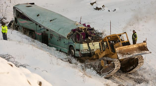 A piece of heavy equipment strains to move a bus which plummeted 200 feet down an embankment in rural Eastern Oregon Sunday, killing nine and sending multiple to hospitals, Monday, Dec. 31, 2012. Surv