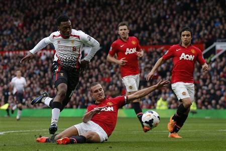 Manchester United's Vidic fouls Liverpool's Sturridge to concede a penalty and be sent off during their English Premier League soccer match in Manchester