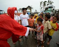 A foreign-volunteer dressed as Santa Claus distributes goodies during Christmas day to children-survivors of the super Typhoon Haiyan in the streets of Tacloban city, Leyte province, on December 25, 2013