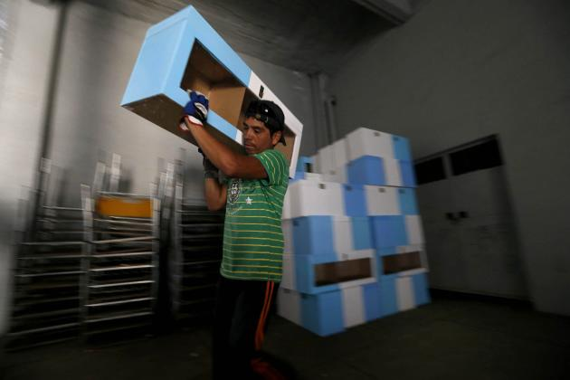 A worker carries ballot boxes at the National Stadium which will be used as a voting station for the upcoming presidential elections in Santiago