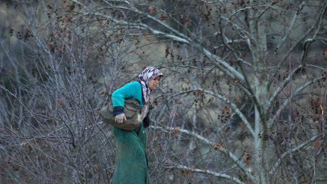 An internally displaced Syrian woman carries her belongings as she is stuck with others in the town of Khirbet Al-Joz, in Latakia countryside, waiting to get permission to cross into Turkey near the Syrian-Turkish border
