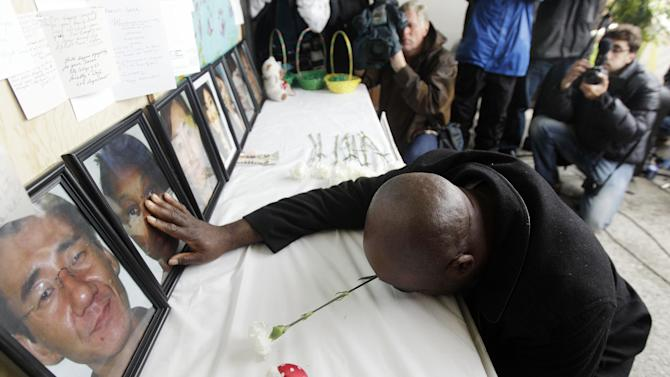 In an April 10, 2012 photo, Efanye Chibuko touches a picture of his wife Doris during a memorial at Oikos University in Oakland, Calif. Doris Chibuko was among the victims of a shooting rampage at the Oakland school. some students at a California Christian college on Monday April 23, 2012, will resume attending classes in a building where seven people were killed   (AP Photo/Marcio Jose Sanchez)