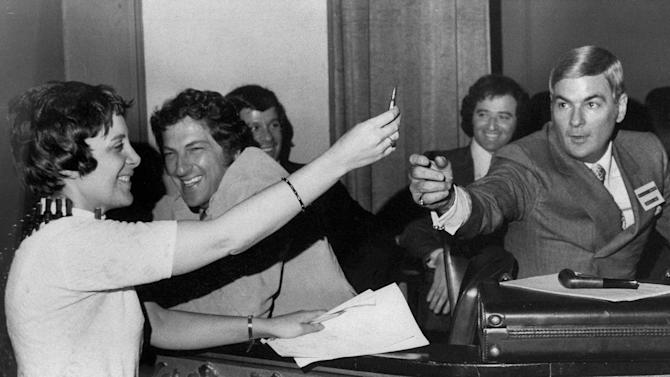 """FILE - In this May 18, 1971 file photo, Evelyn Y. Davis, holds up a bullet from an ammunition bandolier she wore to a shareholders meeting of 20th Century-Fox Film Corp. in Wilmington, Del. as company official Charles M. Lewis reaches for it. Davis, commenting on the election of a new board of directors said, """"Here, fight it out."""" For decades, Davis, who has been buying a few shares of big companies, attends their annual meetings, turning them into her personal stage. But in 2012, Davis didn't show up at any company's annual meeting. Age has finally made her do what the most powerful CEOs in America couldn't: Give it a rest. """"I'm not so young anymore,"""" said Mrs. Davis, 82. (AP Photo)"""