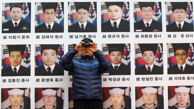 """A war veteran takes picture near the portraits of the sailors killed while on duty onboard South Korean warship, """"Cheonan,"""" which was sunken by North Korea in March 2010 near the sea border, during an anti-North Korea protest rally in Seoul, South Korea, Friday, March 16, 2012. North Korea announced it will launch a long-range rocket mounted with a satellite in honor of late President Kim Il Sung's April birthday. (AP Photo/Lee Jin-man)"""