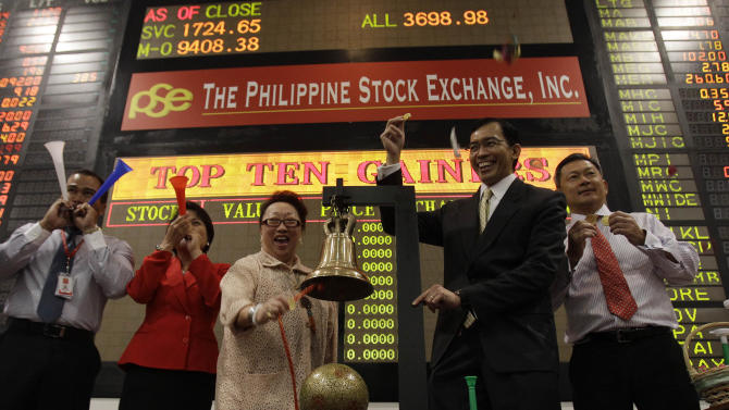 Philippine Stock Exchange President and CEO Hans Sicat, second from right, gestures as PSE treasurer Ma. Vivian Yuchengco rings the bell to signal the start of the first day of trading at Philippine Stock Exchange at the financial district of Makati, south of Manila, Philippines on Wednesday Jan. 2, 2013. Stock markets in Asia registered relief Wednesday over the U.S. congressional vote to stop hundreds of billions of dollars in automatic tax increases and spending cuts that risked plunging the world's biggest economy into recession. (AP Photo/Aaron Favila)