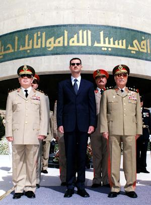 FILE - In this Oct. 6, 2002 file photo, Syrian President Bashar Assad, center, with Syrian Defense Minister Mustafa Tlass, right, and Hassan Turkmany, Chief of Staff, visit the tomb of the unknown soldier, in Damascus, on the occasion of the 29th anniversary of their Liberation War, when Syria and Egypt launched surprise attacks against Israel on Oct. 6, 1973. A top general who has abandoned President Bashar Assad's regime was a longtime friend from Syria's most powerful Sunni family, and his break with the inner circle signals crumbling support from a privileged elite. Brig. Gen. Manaf Tlass was a commander in the powerful Republican Guard and the son of former defense minister Mustafa Tlass, who held the post for 32 years until he retired in 2004.(AP Photo/Sana, File)