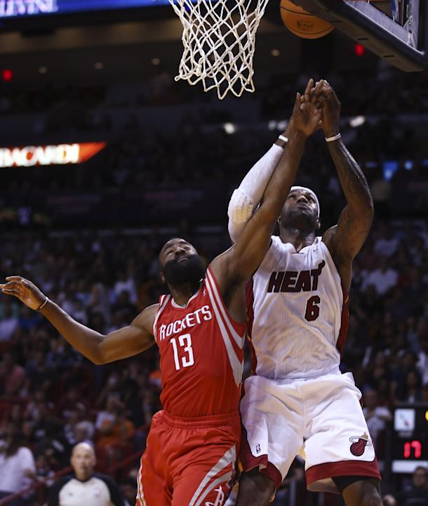 Houston Rockets' James Harden (13) tries to block Miami Heat's LeBron James (6) during the first half of an NBA  basketball game in Miami, Sunday, March 16, 2014