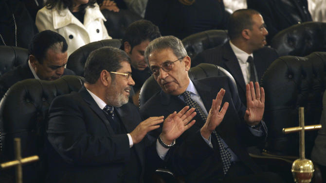 FILE - In this Friday, Jan. 6, 2012 file photo, Mohamed Morsi, left, of Egypt's Muslim Brotherhood and Egyptian presidential hopeful Amr Moussa, right, talk before Christmas Eve mass, led by Coptic Pope Shenouda III at the Coptic cathedral in Cairo, Egypt. The elimination of several top contenders from Egypt's presidential race erodes the chances of an Islamist candidate seizing the country's top job. The Muslim Brotherhood, the most powerful political group to emerge from last year's uprising, finds itself increasingly in a bind, jostling for power with the ruling generals and with liberal, secular groups fearful of domination by religious parties. (AP Photo/Maya Alleruzzo, File)