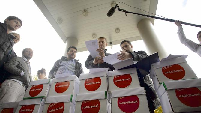 Alexei Navalny, centre, addresses the media, outside a court, in Moscow, on Thursday, Sept. 12, 2013. Opposition activist Alexei Navalny appeared at a Moscow courthouse to start a lawsuit contesting the results of Moscow's mayoral election, which he lost to the Kremlin-backed incumbent. Navalny arrived with more than 50,000 pages of documents to court on Thursday to support his claim that there had been violations at the polls. (AP Photo/Evgeny Feldman)