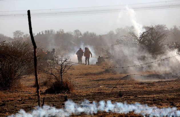 Striking mineworkers are caught in teargas as police open fire on striking miners at the Lonmin Platinum Mine near Rustenburg, South Africa, Thursday, Aug. 16, 2012. An unknown number of people have been killed and injured. Police moved in on workers who gathered on a rocky outcropping near the Lonmin late afternoon, firing unknown ammunition and teargas. (AP Photo) SOUTH AFRICA OUT