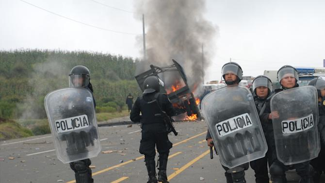 National Civil Police agents stand near a military truck in flames during clashes with peasants protesting against the cost of electricity in Santa Catarina Ixtahuacan, west of Guatemala City on Thursday Oct. 4, 2012. At least two people have been killed and dozen others seriously wounded in the confrontation between protesters and security forces. (AP Photo)