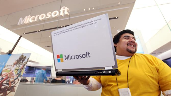 Microsoft store employee Mykal Carlton picks up his laptop sporting the new company logo, while also wearing a shirtt matching one of the four featured colors, and heads over to assist a customer Thursday, Aug. 23, 2012, in Seattle. Microsoft's new corporate logo sets the stage for a wave of products designed to cast the world's largest software maker in a new light. The makeover unveiled Thursday marks the first time that Microsoft Corp. has revamped its logo since February 1987. The Internet was barely around then, and cellphones were considered a luxury. (AP Photo/Elaine Thompson)