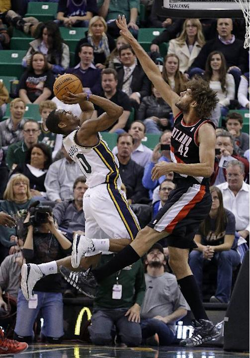 Utah Jazz's Alec Burks, left, shoots as Portland Trail Blazers' Robin Lopez (42) defends in the second quarter in an NBA basketball game Monday, Dec. 9, 2013, in Salt Lake City