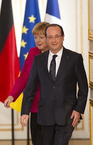 French President Francois Hollande, left, arrives with German Chancellor Angela Merkel at their press conference after a meeting at the Elysee Palace, Paris, Thursday May 30, 2013. (AP Photo/Jacques Brinon)