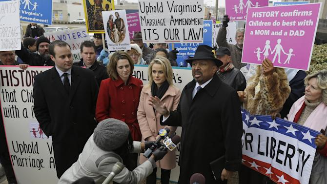 Former Republican lieutenant governor candidate E.W. Jackson, front right, speaks to the media during a demonstration outside federal court in Norfolk, Va., Tuesday, Feb. 4, 2014. Jackson spoke in favor of the law banning same-sex marriage. A federal judge will hear arguments Tuesday on whether Virginia's ban on gay marriage is unconstitutional. The state's newly elected Democratic attorney general has already decided to side with the plaintiffs and will not defend the ban. (AP Photo/Steve Helber)