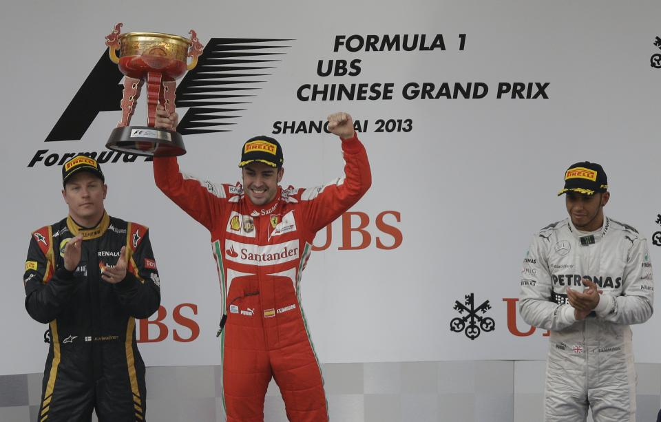 Ferrari driver Fernando Alonso of Spain holds his trophy aloft after winning the Chinese Formula One Grand Prix in Shanghai, China, Sunday, April 14, 2013. Lotus driver Kimi Raikkonen, left, of Finland was second and Mercedes driver Lewis Hamilton, right, of Britain  finished third. (AP Photo/Mark Baker)