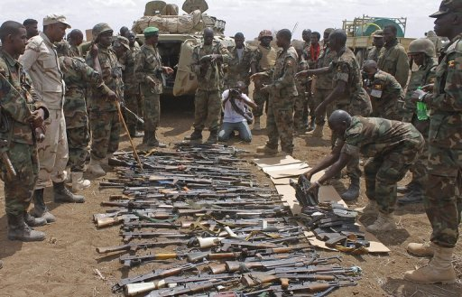 <p>AU soldiers from Uganda look at weapons recovered from members of Somalia's Al-Qaeda-linked Shebab after they gave themselves up in Garsale, some 10km from Jowhar, in September 2012. African Union troops and Somali forces seized the formerly Islamist-held town of Jowhar Sunday, wresting control of one of the largest remaining towns held by the Shebab, officials said.</p>