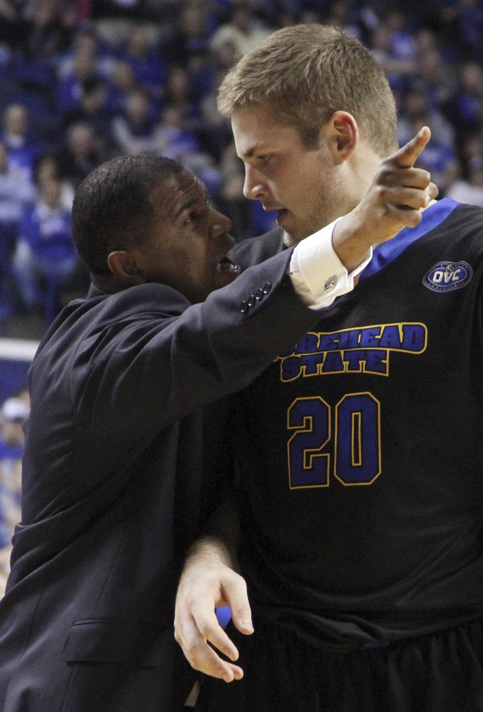 Morehead State coach Sean Woods, left, gives pointers to Chad Posthumus during the first half of an NCAA college basketball game against Kentucky at Rupp Arena in Lexington, Ky., Wednesday, Nov. 21, 2012. (AP Photo/James Crisp)
