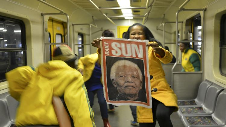 A woman holds a poster of former South African President Nelson Mandela at Johannesburg's Park Station on her way to the Memorial Service for Mandela at the First National Bank Stadium, also known as Soccer City