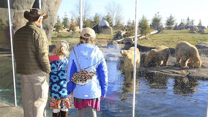 Jack Hanna, left, director emeritus of the Columbus Zoo and Aquarium, watches the polar bears with Make-A-Wish child Anna, right, 11, and her sister Sarah Grace, 8, during Anna's day as a zookeeper Friday, Dec. 14, 2012, in Columbus, Ohio. Anna's wish to be a zookeeper with Jack Hanna was granted as Macy's celebrates National Believe Day. (Jay LaPrete/AP Images for Macy's)