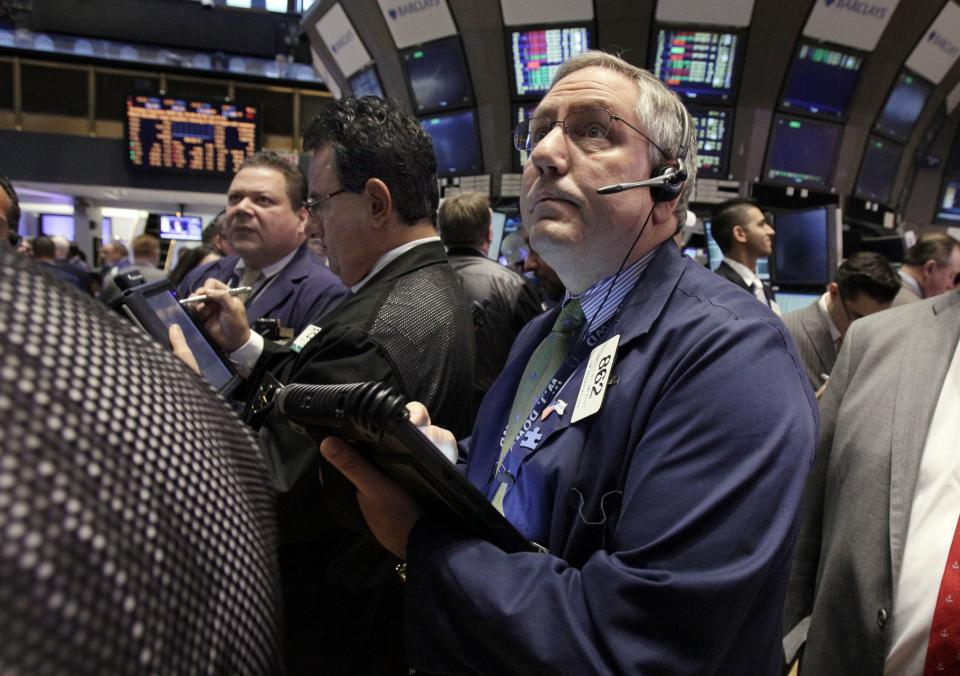 Trader Warren Meyers, right, works on the floor of the New York Stock Exchange Monday, April 2, 2012. Wall Street was poised for a flat opening Tuesday April 3, 2012 following Monday's stellar gains — both the Dow futures and the S&P 500 futures were 0.1 percent lower.  (AP Photo/Richard Drew)