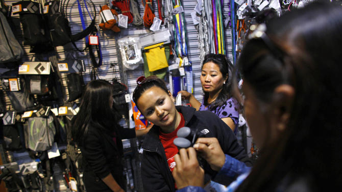 In this Tuesday, Feb. 21, 2013 photo, 29-year-old team leader Shailee Basnet looks at climbing gear at a store in Katmandu, Nepal. Aiming to change the all-male image of mountaineering in the country, a group of Nepalese women have embarked on a mission to climb the tallest mountain on each of the seven continents. The women, aged between 21 and 32, have already climbed Everest in Asia, Kosciuszko in Australia and Elbrus in Europe and are preparing next week to climb Mount Kilimanjaro in Africa to mark International Women's Day. (AP Photo/Niranjan Shrestha)