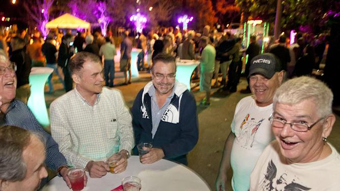 Friends share stories with each other at the Wilton Manors Out of the Closet (OTC) Block Party & Insti-Test Launch Marking the 5th anniversary of Wilton Manors OTC in Wilton Manors, Florida on Saturday, February 2nd, 2013 at the Hagan Park/City Hall parking lot in Wilton Manors, FL. (Mitchell Zachs /AP Images for AIDS Healthcare Foundation)