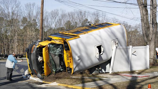 An investigator examines an overturned school bus resting on a fence after colliding with a commuter bus Thursday, Jan.10, 2013, in Old Bridge, N.J.  The New York City-bound commuter bus and the mini school bus crashed on a state highway in New Jersey, injuring at least 17 people, two critically.  School officials said no students were on the Old Bridge school bus, which landed on its side along Route 9.  (AP Photo/Mel Evans)