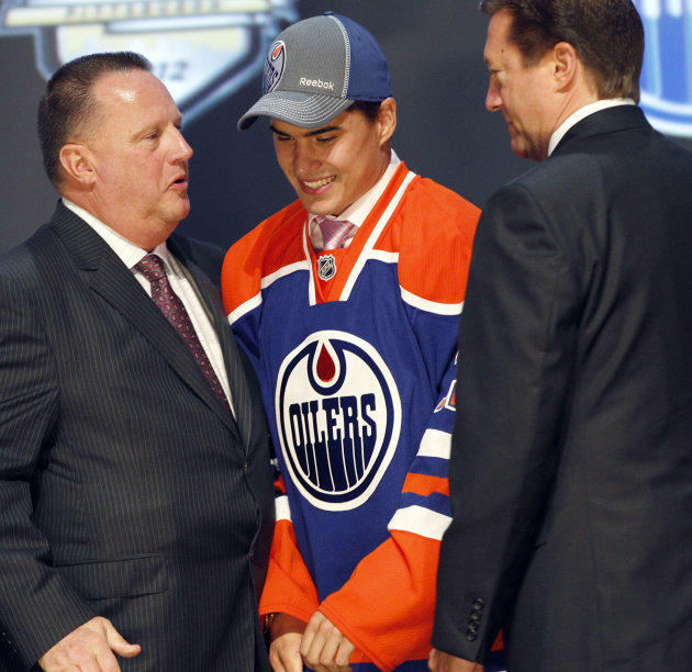 Nail Yakupov, center, a winger from Russia who was chosen first overall by the Edmonton Oilers in the first round of the NHL hockey draft,  stands with Oilers officials on Friday, June 22, 2012, in Pi