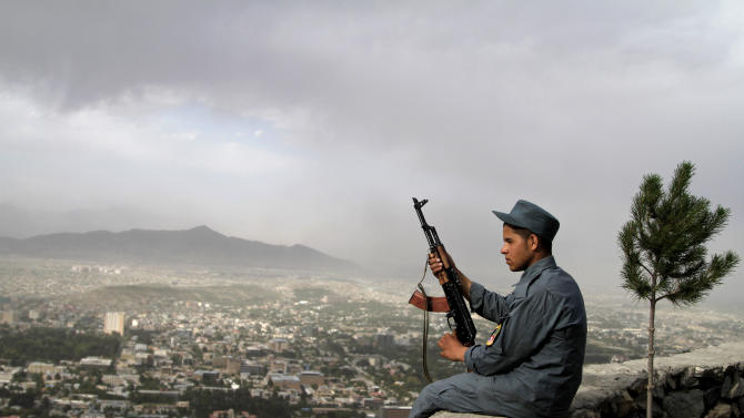 An Afghan policeman sits on a wall on a mountain overlooking Kabul, Afghanistan, Wednesday, May, 22, 2013. (AP Photo/Ahmad Jamshid)