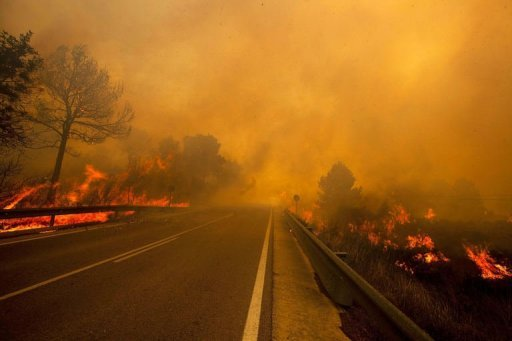 &lt;p&gt;A wildfire spreads around a road in Yatova, near Valencia. More than 1,300 Spanish firefighters and 30 water-bombing aircraft and helicopters Saturday sought to contain wildfires that have razed vast forest areas and threatened villages.&lt;/p&gt;