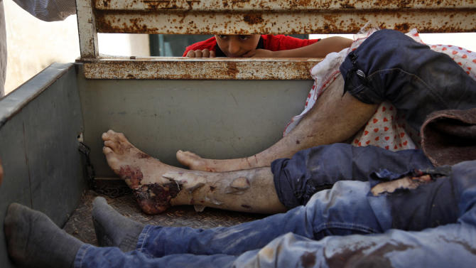 A Syrian boy looks at the bodies of nine Syrians on a truck after they were found dead in an open field and taken to the town of Anadan outskirts of Aleppo, Syria, Monday, Aug. 6, 2012. (AP Photo)