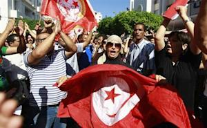 Anti-government protesters wave Tunisian flags as they rally for the dissolution of the Islamist-led government in Sfax