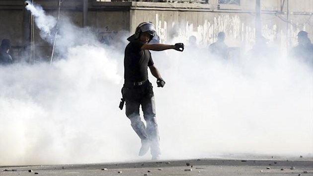 A riot policeman throws a tear gas canister which was thrown back by protesters in Cairo
