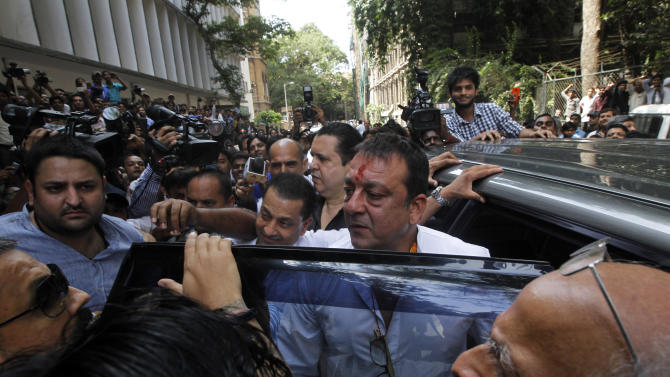 Bollywood star Sanjay Dutt, center, arrives to surrender before a court in Mumbai, India, Thursday, May 16, 2013. Dutt has been sentenced to five years in prison for a 1993 weapons conviction linked to a deadly terror attack in Mumbai that killed 257 people. The 53-year-old actor served 18 months in jail before being released on bail in 2007 pending an appeal. The Supreme Court reduced his prison sentence to five years from the six-year term initially handed down. (AP Photo/Rajanish Kakade)