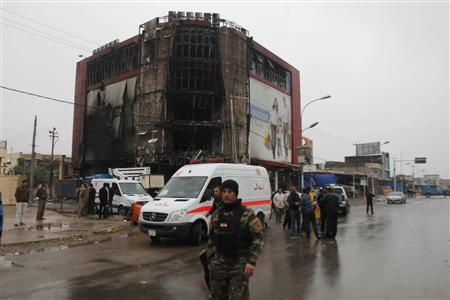 Iraqi security forces personnel inspect the site following an attack by gunmen and suicide bombers on a police intelligence headquarters and a shopping mall in Kirkuk