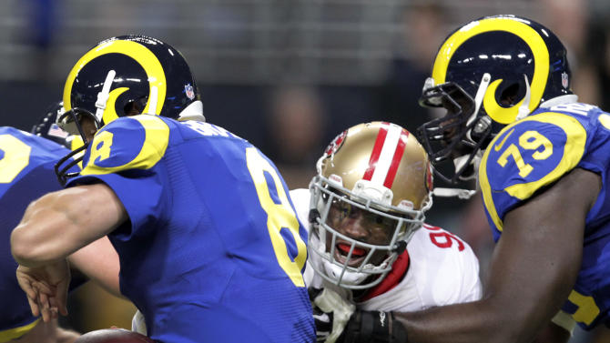 San Francisco 49ers outside linebacker Aldon Smith, center, sacks St. Louis Rams quarterback Sam Bradford, left, for a 6-yard loss while  Rams tackle Barry Richardson, right, tries to block Smith during the second quarter of an NFL football game Sunday, Dec. 2, 2012, in St. Louis. (AP Photo/Tom Gannam)
