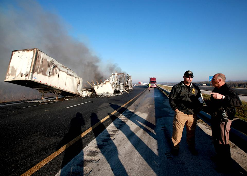Officials work at the scene of a multi-vehicle wreck on Interstate 75 at Paynes Prairie on Sunday, Jan. 29, 2012, south of Gainesville, Fla. (AP Photo/The Gainesville Sun, Matt Stamey)