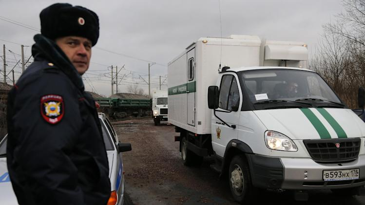A Russian police officer guards police vans believed to be transporting Greenpeace activists to a prison in St. Petersburg, Russia, Tuesday, Nov. 12, 2013. Jailed Greenpeace activists have been transferred from Russia's far north to the city of St. Petersburg, officials confirmed. (AP Photo/Dmitry Lovetsky)