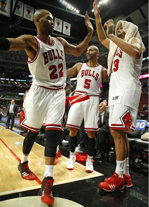 Chicago Bulls forward Taj Gibson (22) celebrates the win against the Miami Heat with forward Carlos Boozer (5) and center Joakim Noah (13) at the end of an NBA basketball game in Chicago, Thursday, De