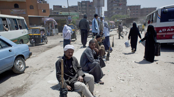 In this Wednesday, April 24, 2013 photo, Egyptian day laborers wait for employers at a street in Cairo, Egypt. Egypt has been increasingly knocking on doors around the world seeking billions to fill rapidly draining coffers. But not everyone is eager to give, and economists fear that quick injections of cash only let the government put off painful economic reform. (AP Photo/Nasser Nasser)