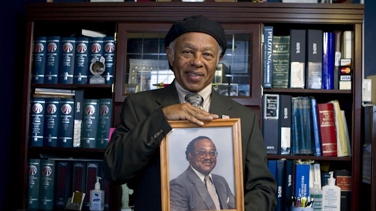 In this May 16, 2013, photo, Abdulah Salim, Jr. hold the photograph of his father Dr. Reginald A. Hawkins who was a prominent Charlotte civil rights leader, in Silver Spring, Md. In the spring of 1963, a Hawkins led 65 people on a four-mile march from an African American college to the center of Charlotte's downtown. ( AP Photo/Jose Luis Magana)